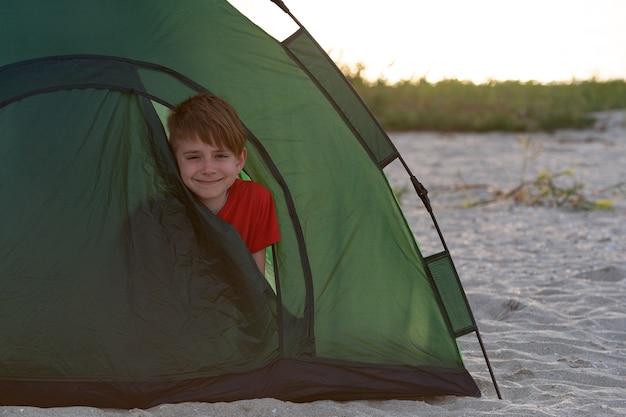 Chłopiec wyglądający z namiotu turystycznego. aktywne wakacje. kemping.