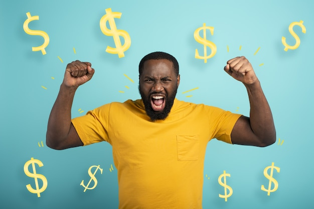 Chłopiec wygrywa pieniądze zdumiony i zdziwiony wyraz twarzy o jasnoniebieskiej powierzchni
