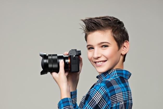 Chłopiec z aparatem fotograficznym robienia zdjęć. portret kaukaski chłopiec z aparatem cyfrowym w rękach