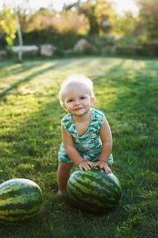Chłopiec z arbuza obsiadaniem na trawie