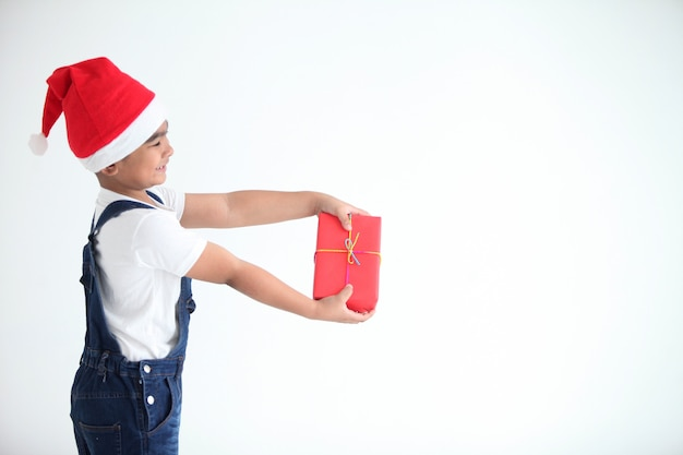 Chłopiec z białą koszulą i niebieskim dżinsy i czerwony kapelusz gospodarstwa czerwone pudełko