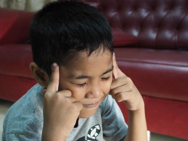 Chłopiec z bólem głowy na tle czerwonej sofy w domu.