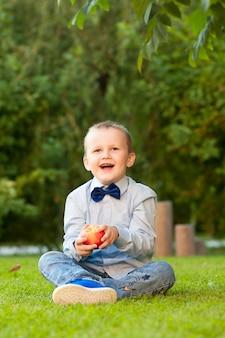 Chłopiec z brzoskwiniami w parku