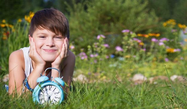 Chłopiec z budzikiem kłaść w ogródzie