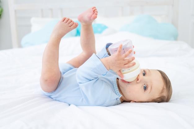 Chłopiec z butelką mleka na łóżku do spania w niebieskim body, koncepcja żywności dla niemowląt
