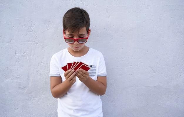 Chłopiec z czerwonymi okularami przeciwsłonecznymi, grając w pokera