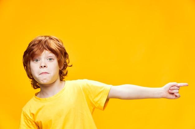 Chłopiec z czerwonymi włosami widok z przodu w żółtej koszulce wskazuje z boku