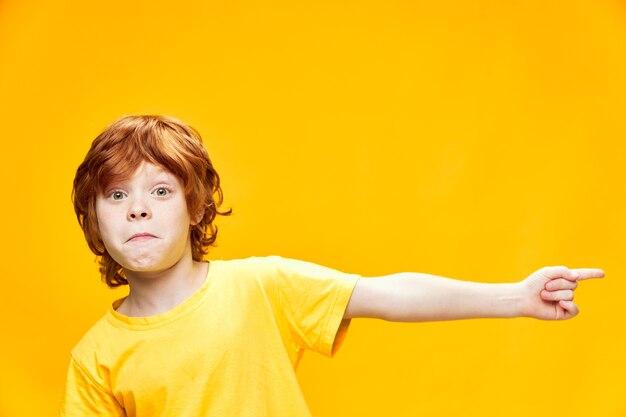 Chłopiec z czerwonymi włosami widok z przodu w żółtej koszulce wskazywać z boku palcem wskazującym kopiowanie miejsca z bliska