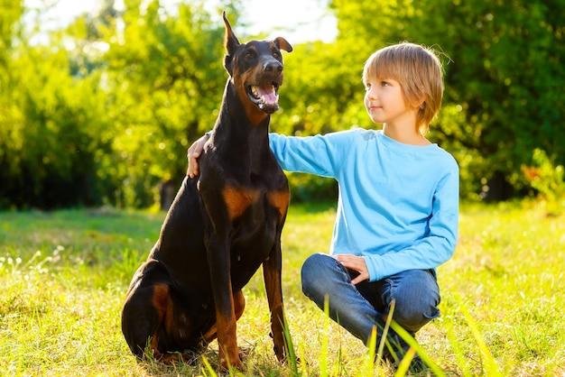 Chłopiec z dobermannem w letnim parku.