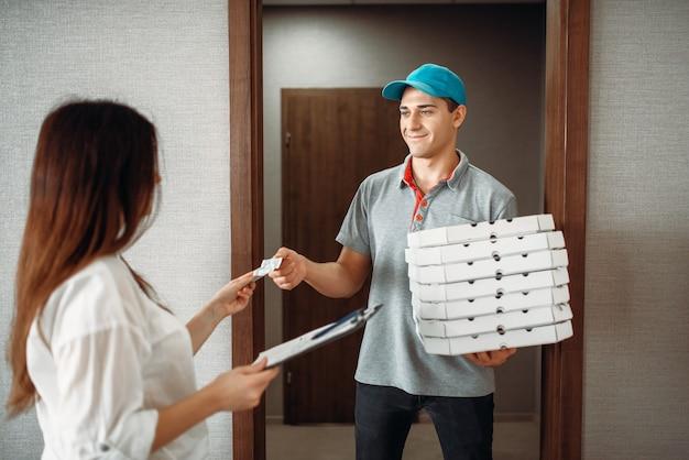 Chłopiec z dostawcą pizzy bierze napiwek od klientki