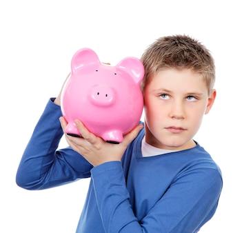 Chłopiec z dużą różową skarbonką na białej przestrzeni