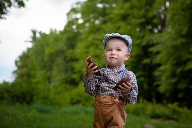 Chłopiec z dużym czekoladowym jajkiem w naturze