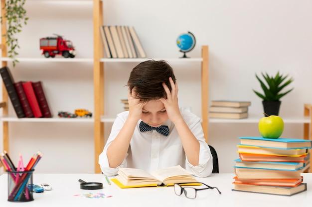 Chłopiec z dużym kątem skoncentrowany na czytaniu
