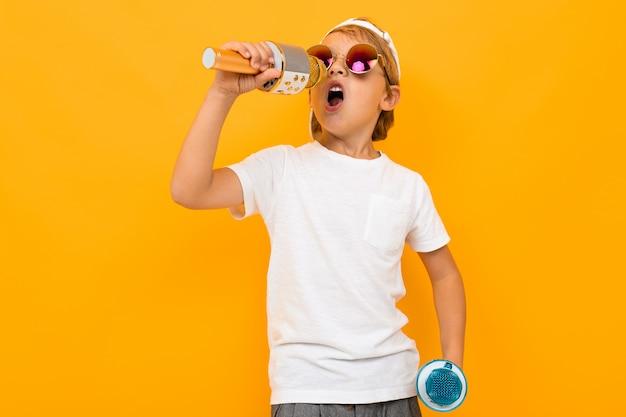 Chłopiec z dwoma mikrofonami śpiewa na jasnej żółtej ścianie