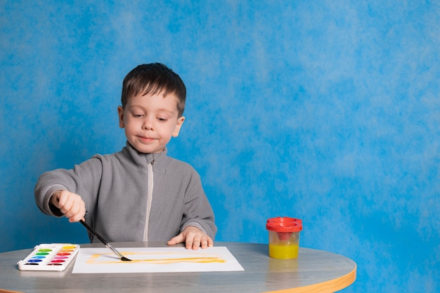 Chłopiec z farbami na gładkiej ścianie. szczęśliwe dzieciństwo. rysunek hobby. rysunek dla dzieci. farby dla dzieci.