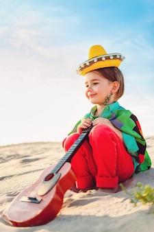 Chłopiec z gitarą siedzi na piasku