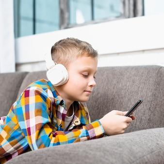 Chłopiec z hełmofonami używać smartphone