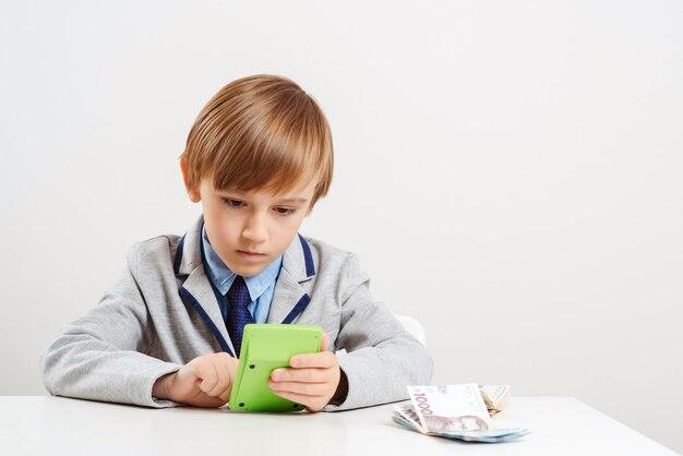 Chłopiec z kalkulatorem rozlicza pieniądze. przyszła edukacja.