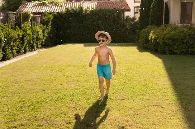 Chłopiec z kapeluszem i okularami przeciwsłonecznymi