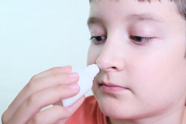 Chłopiec z katarem trzyma w dłoni lekarstwo, iryguje sprayem do nosa, aby zatrzymać alergiczny nieżyt nosa i zapalenie zatok.