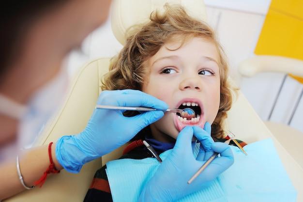 Chłopiec z kędzierzawym czerwonym włosy w błękitnym stomatologicznym krześle. dentysta dziecięcy
