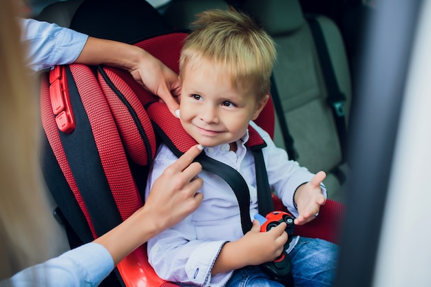 Chłopiec z kędzierzawym włosy obsiadaniem w dziecięcym samochodowym siedzeniu z zabawkarskim samochodem w rękach