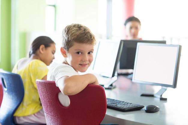 Chłopiec z kolegami i nauczycielem w sali komputerowej