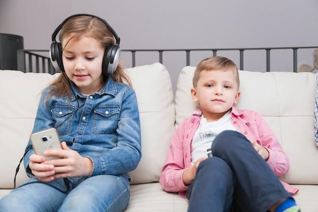 Chłopiec z kontrolerem i dziewczyną z smartphone