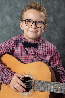 Chłopiec z kraciastą koszulą grając na gitarze akustycznej