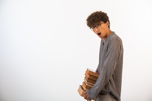 Chłopiec z kręconymi włosami i okularami optique, niosący ciężkie księgi.