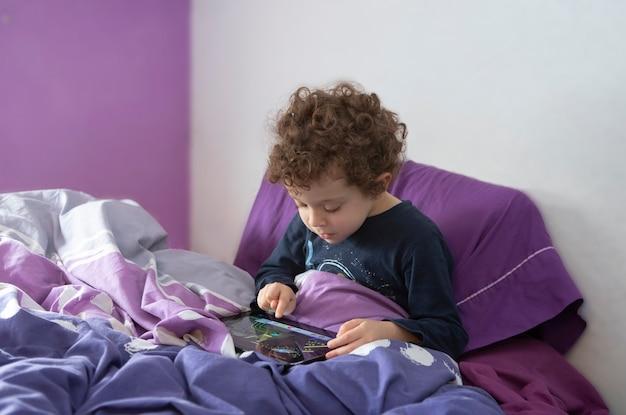 Chłopiec z kręconymi włosami siedzi na łóżku z tabletem w rękach, bawi się i zabawia