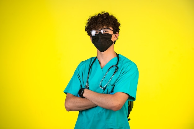 Chłopiec z kręconymi włosami w mundurze medycznym i masce na twarz stoi w pewnej pozycji.