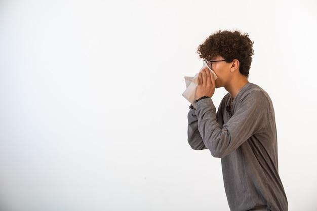 Chłopiec z kręconymi włosami w okularach optique, czyszczący nos chusteczką, widok z profilu.