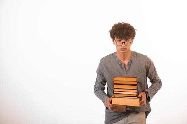 Chłopiec z kręconymi włosami w okularach optique niosący stos książek.