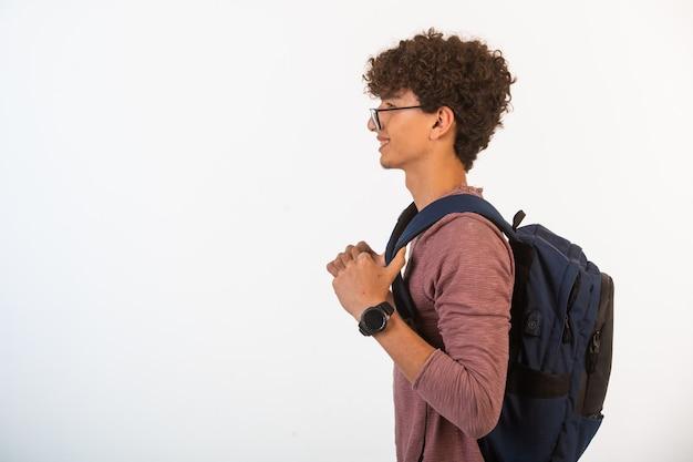 Chłopiec z kręconymi włosami w okularach optique, trzymając plecak w lewo