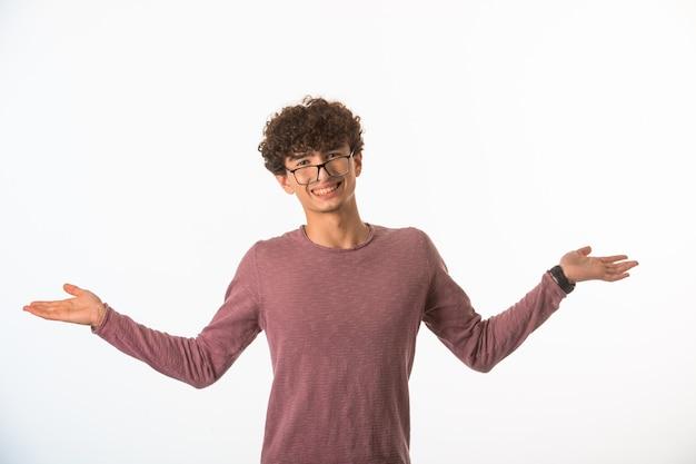 Chłopiec z kręconymi włosami w okularach optique wygląda pewnie i odnosi sukcesy.