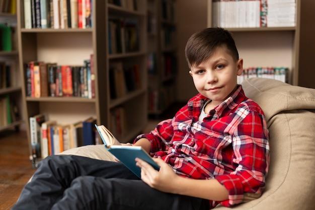 Chłopiec z książką patrzeje kamerę