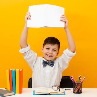Chłopiec z książką podniesioną nad głową