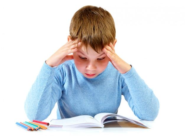 Chłopiec z książką za stołem