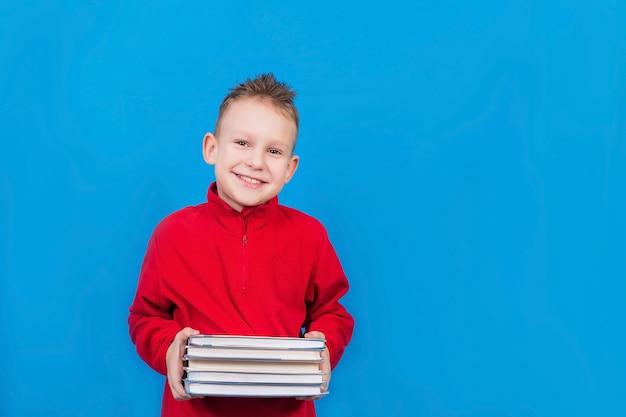 Chłopiec z książkami na niebieskiej powierzchni