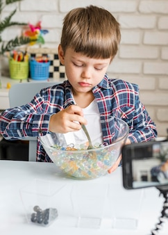 Chłopiec z kulkami hydrożelu w misce