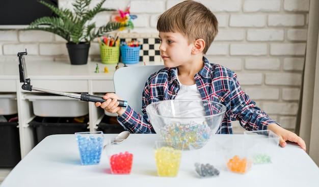 Chłopiec z kulkami hydrożelu w okularach