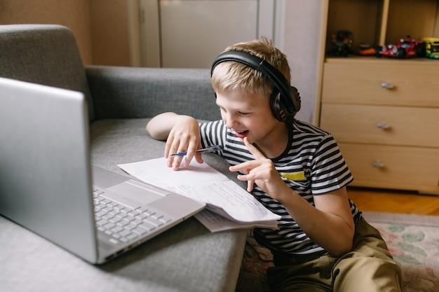 Chłopiec z laptopem odrabiania lekcji ze słuchawkami