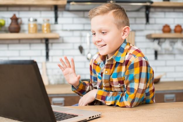 Chłopiec z laptopem w kuchni