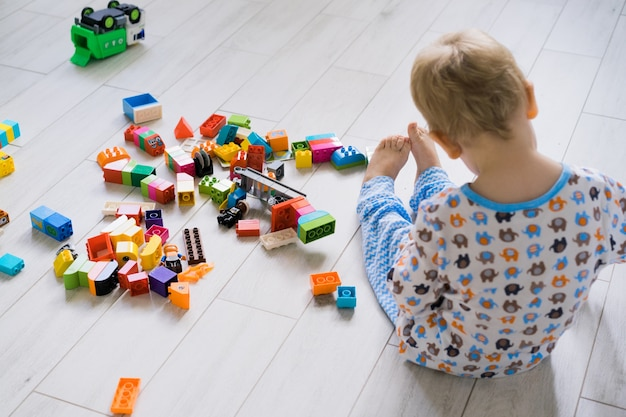 Chłopiec z mamą, grając w kolorowy zestaw budowlany