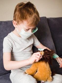 Chłopiec z maską bawić się z zabawką