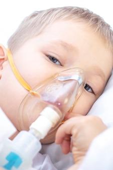 Chłopiec z maską inhalatora. problemy z oddychaniem w astmie. chłopiec z maską inhalacyjną leży w łóżku i oddycha adrenaliną.