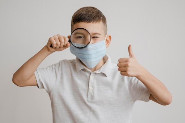 Chłopiec z maską medyczną za pomocą lupy w klasie