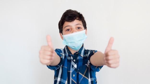 Chłopiec z maską pokazuje ok znaka