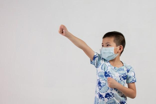 Chłopiec z maską pozuje na białym tle